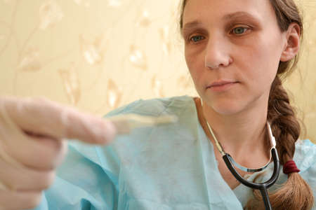 A female doctor looks at a thermometer to determine the high temperature for a patient's disease 스톡 콘텐츠