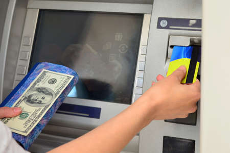 A woman inserts a plastic card into an ATM to withdraw cash