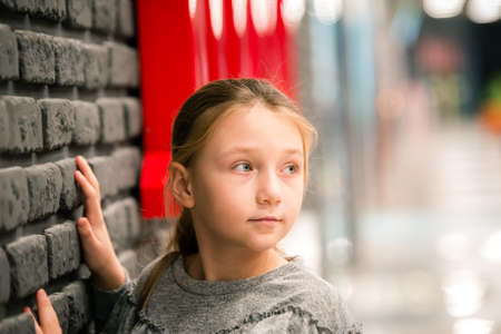 A teenage girl stands by a brick wall and looks away