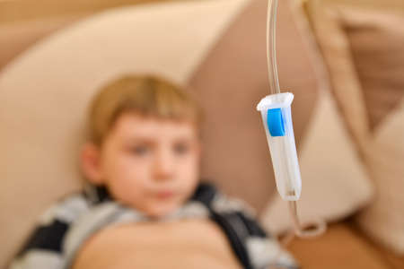 The child at home lies under a dropper, injections to the child with an infectious disease