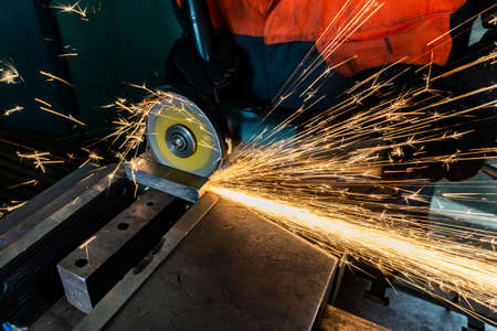 A worker cuts off a workpiece with a grinder, sparks fly on opposite sides