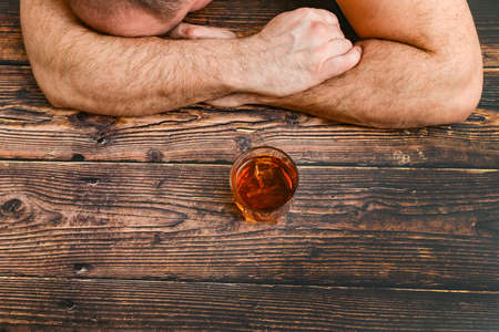 A drunk man is sleeping on a wooden table after intoxication, next is a glass of cognac, whiskey, brandy. The concept of alcoholism and alcohol dependence Foto de archivo