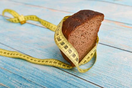 A piece of black bread, wrapped in a yellow centimeter, is swiftly rushing forward for a healthy lifestyle. The concept of weight loss and healthy eating