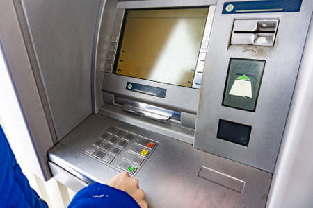 A woman at an ATM presses a button to withdraw cash Stock fotó
