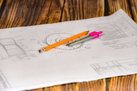 Pencil, compass and technical drawing on a dark wooden background