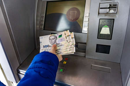 A woman at an ATM holds 500 hryvnia notes in her hand