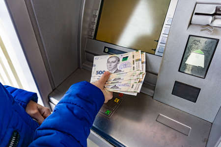 A woman at an ATM withdraws cash hryvnias in Ukraine, 100 and 500 hryvnia notes Stock fotó