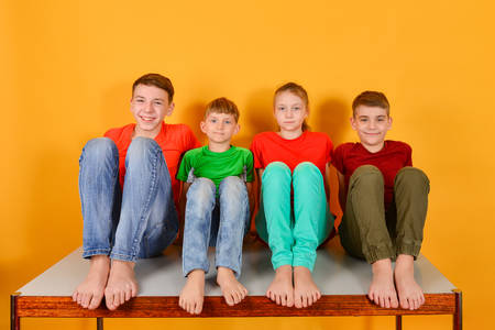 Four children squatting barefoot, a bright colorful juicy photo of teenagers sitting in colored clothes