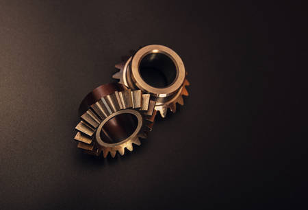 Two bevel gears on a black background, advertising of manufactured products at a gear-cutting enterprise