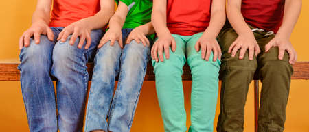 Four children in bright and colorful clothes are sitting with their legs dangling and hands on their knees, on a yellow background