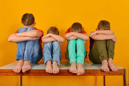 Barefoot children sit with their legs crossed and hugging their knees. Four children lowered their heads down Stockfoto - 140155053