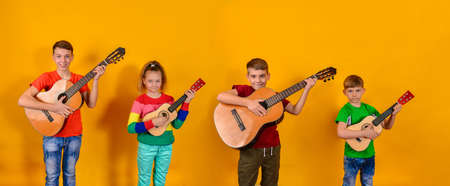 Four children with acoustic guitars in bright and colorful clothes stand in a row on a yellow background