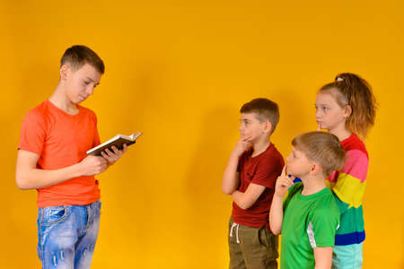 The guy reads the children from the book, while younger brothers and sisters listen to him carefully and thoughtfully