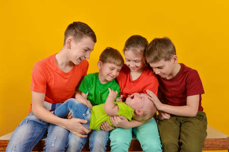 Four children hold a small child in their arms, happy and joyful brothers and sisters 版權商用圖片