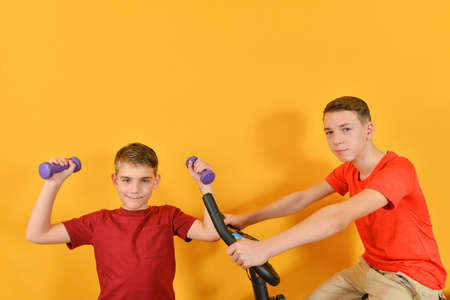 Two athletic brothers perform cardio exercises, a boy is odd with dumbbells, the other is sitting on a stationary bike