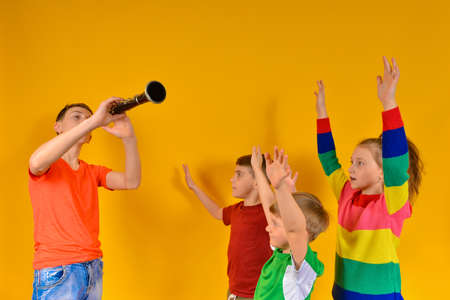 Children's choir accompanied by clarinet. The boy plays the clarinet to the children, and they sing and raise their hands up