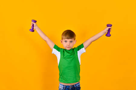 A boy in a green sports shirt holds his hands with dumbbells on the sides, a sports child on a yellow background