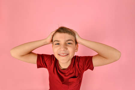 Funny boy in a burgundy T-shirt holds his head with his hands on a pink background, wide angle photo with geometric distortions