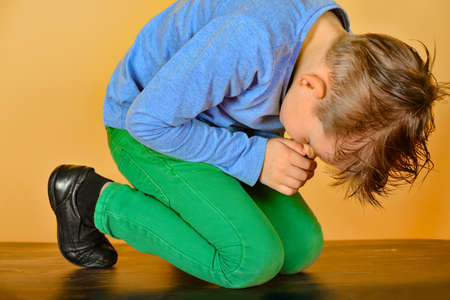 The boy bowed in prayer before God. The child is kneeling in the prayer of repentance before the Supreme Creator Stock Photo