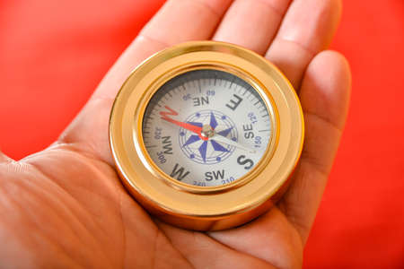 A man holds a compass in his hand for knowing the direction of the path, a traveler on the road learns the compass navigation