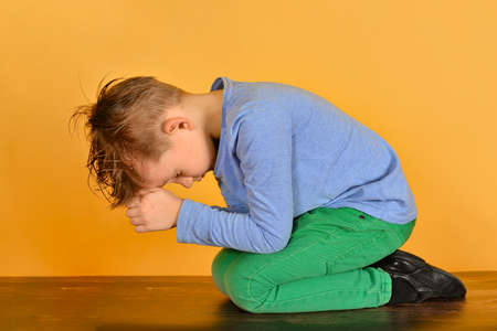 The boy bowed in prayer before God. The child is kneeling in the prayer of repentance before the Supreme Creator
