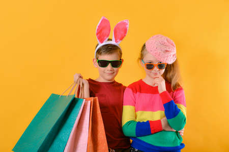 Boy and girl in bright and colorful clothes and sunglasses with shopping bags, concept of children's shopping.