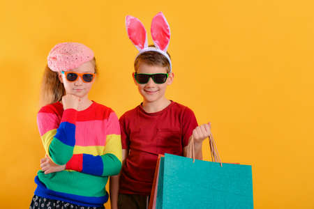 A boy with rabbit ears stands next to his sister and holds empty shopping bags, concept of children's shopping for the holiday.