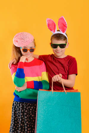 Boy with a girl in bright and colored clothes with shopping bags, concept of children's shopping.
