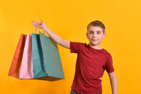 The boy raised his hand with shopping bags up. Joyful and happy buyer.