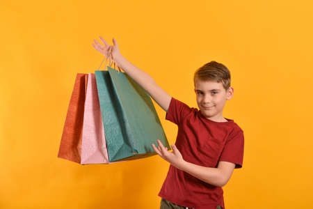 A joyful guy holds shopping bags in his hand over his head and shows with his hand the goods. Joyful and happy buyer.