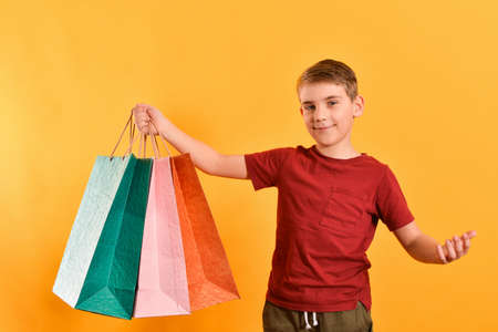 Joyful guy holds shopping bags in his hand.