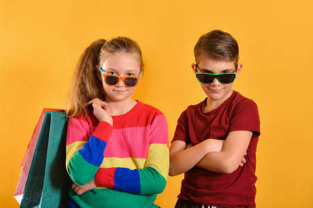 Boy and girl in sun glasses and with shopping bags, on a yellow background. Imagens