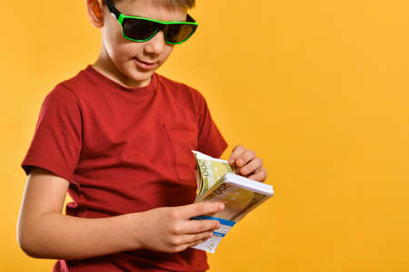 A boy in sunglasses considers banknotes in a bundle, a glamorous and stylish child with currency on a yellow background.