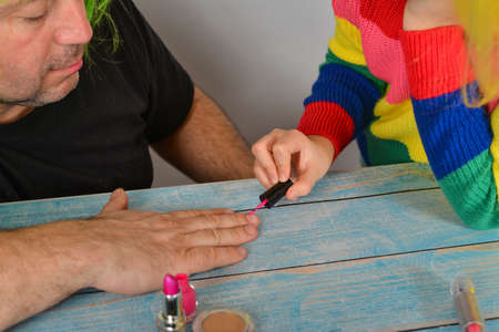 A father in a wig gives his daughter a hand. girl paints her father's nails.