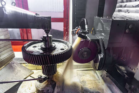 Gear grinding machine in operation, grinding of teeth of a wheel with oil cooling under pressure.