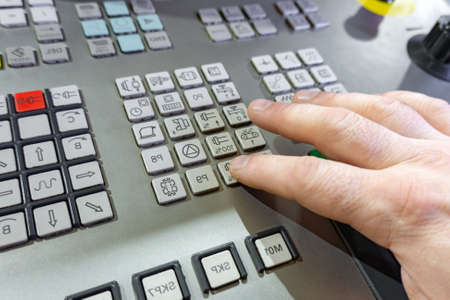 The worker switches the buttons on the remote control of the CNC machine, the control of the processing center.