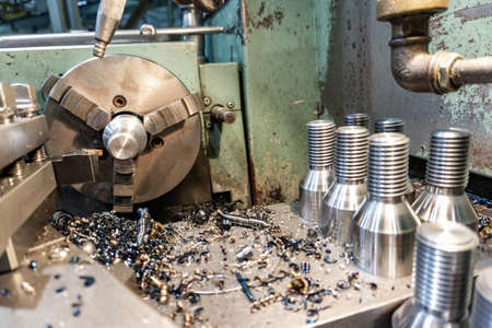 Bolt threading on a lathe in a machine shop, finished products on a machine bed. 스톡 콘텐츠