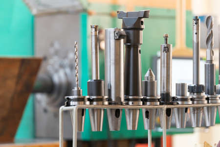 Conical and collet mandrels with cutters and drills on the rack, accessories for the milling machine. 스톡 콘텐츠