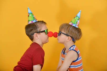 Two brothers in holiday caps with a clown nose stand close to each other.