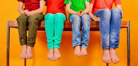 Children are sitting on the table, legs hanging down. Four teenage children show their knees and legs barefoot. Stock Photo