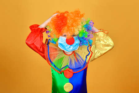 Sad child clown in a protective medical mask against coronavirus on a yellow background holds his hands behind his head and does not know what to do next.