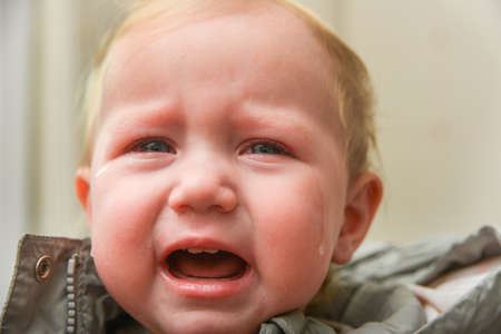 The child is crying with tears in his eyes, children's problems. 스톡 콘텐츠