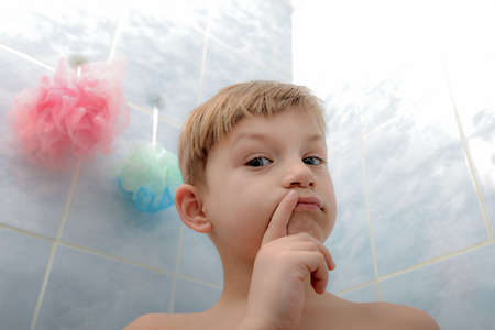 The child in the shower room thinks what kind of washcloth he should choose and what he will do now.