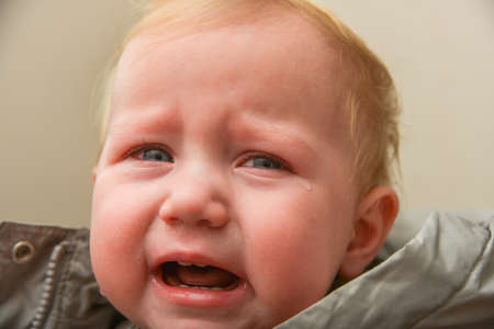 The child is crying with tears in his eyes, childrens problems.