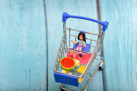 Cart with a doll, toy products are in the consumer basket.