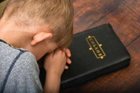 The boy reads the Bible and prays, worshiping the child in spirit and truth.