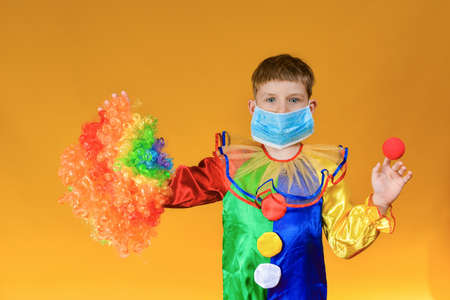 A sad and sad baby clown in a protective medical mask from a coronavirus holds a colored wig in one hand and the clowns nose in the other.