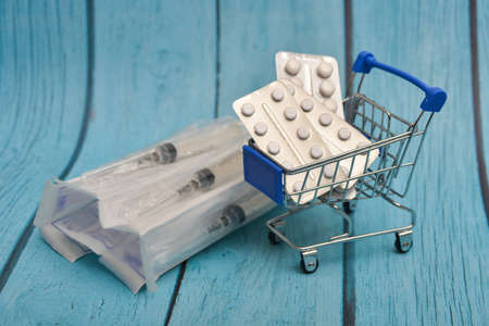 Cart with medicines, pills, antibiotics, vitamins, antiviral agents in a consumer basket on a background of syringes.
