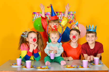 Five children are sitting at the festive table with a clown in a carnival costume.