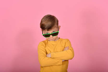 Glamorous and stylish boy posing for the camera, model in sunglasses, in yellow clothes in the studio on a pink background. Фото со стока